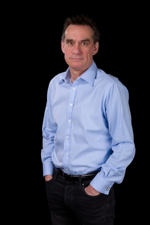mid adult men: Portrait of Smiling Relaxed Middle Age Business Man in Blue Shirt Black Background