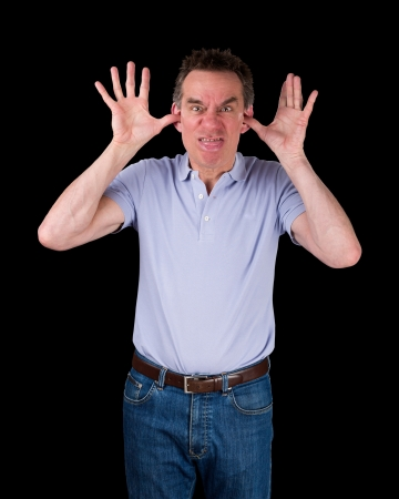 poking: Angry Middle Age Man Poking Out Tongue with Hands in Ears Black Background Stock Photo