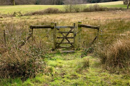 Closed Old Rustic Gate in Green Grassy Countryside on Sunny Day photo
