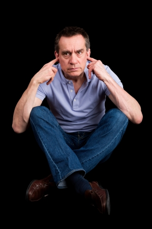 Angry Frowning Middle Age Man Fingers in Ears Not Listening Cross Legged Black Background