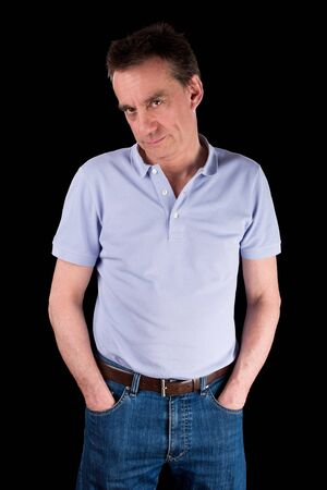 Grumpy Frowning Middle Age Man with Hands in Pockets Black Background photo