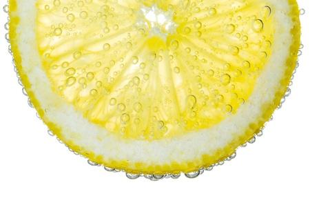 分離された明確な炭酸水バブルのバック グラウンドでレモン スライス 写真素材