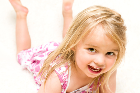 mischevious: Closeup Portrait of Beautiful Toddler Girl Lying Down on Neutral Background