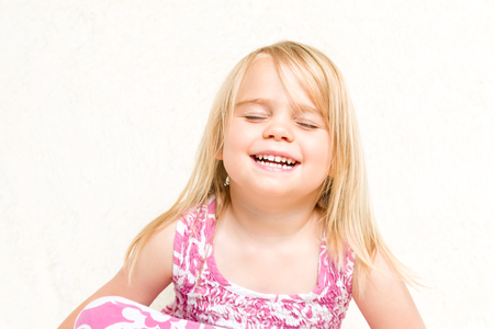 mischevious: Closeup Portrait of Beautiful Laughing Toddler Girl Eyes Closed Neutral Background