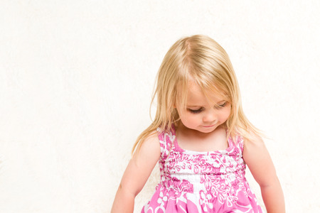 mischevious: Closeup Portrait of Beautiful Toddler Girl Looking Down on Neutral Background Stock Photo