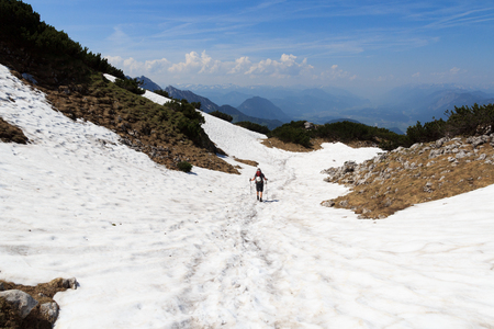 snowfield: Mountaineer descending alone on snowfield Stock Photo