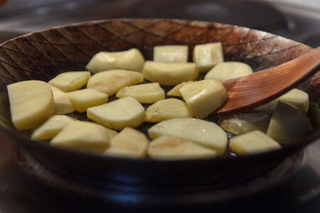 chippy: Chip potatoes in iron frying pan with spatula