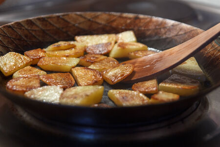 hefty: Chip potatoes in iron frying pan with spatula