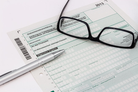 statutory: Form of income tax return with ball pen and glasses Stock Photo