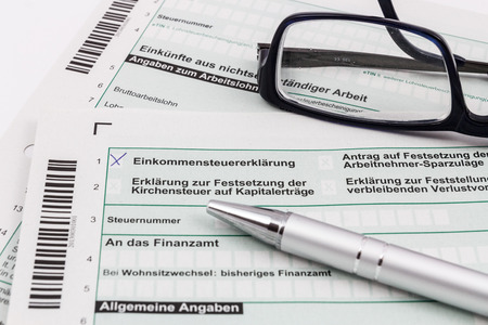 Form of income tax return with ball pen and glasses Imagens