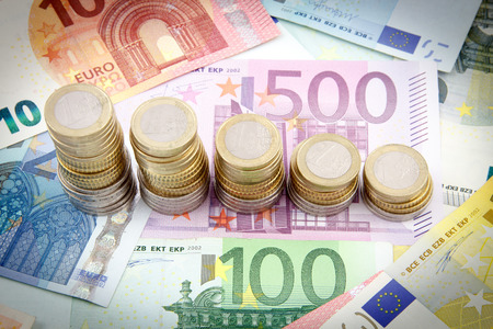 economize: Decreasing stacks of euro coins on euro banknotes Stock Photo