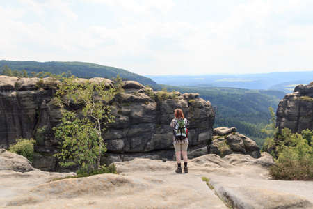 outpost: Female hiker looking at panorama from Affensteine in Saxon Switzerland