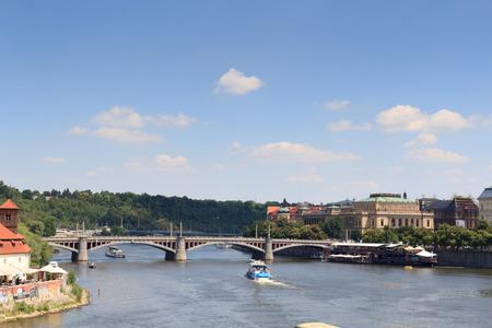manes: Manes Bridge, boats on river Vltava and Czech Philharmonic in Prague Editorial