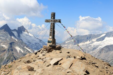 hohe tauern: Summit cross and prayer flag on mountain Kreuzspitze in the Hohe Tauern Alps, Austria