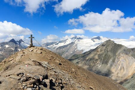 hohe tauern: Summit cross and prayer flag on mountain Kreuzspitze with glacier panorama and Grossvenediger in the Hohe Tauern Alps, Austria Stock Photo