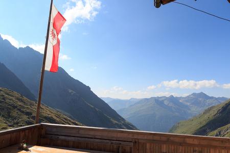 alpine hut: Mountain panorama seen from alpine hut Eisseehutte with Austrian flag in Hohe Tauern Alps, Austria
