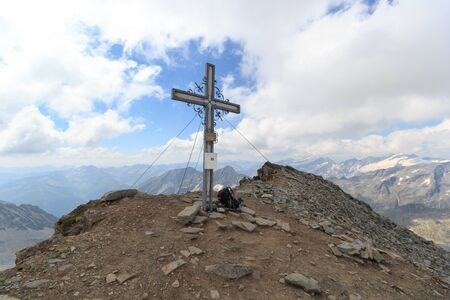 hohe tauern: Summit cross and backpack on mountain Weissspitze with panorama in Hohe Tauern Alps, Austria