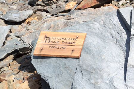 hohe tauern: Wooden sign with German text National park Hohe Tauern - Central zone on a rock in the Alps, Austria