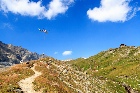 alpine hut: Transport helicopter flying with supplies and mountain panorama with alpine hut in Hohe Tauern Alps, Austria