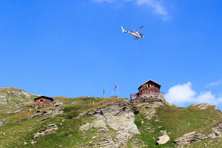 tauern: Transport helicopter flying with supplies and mountain panorama with alpine hut in Hohe Tauern Alps, Austria
