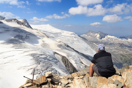 crack climbing: Male mountaineer looking at mountain glacier panorama view with binoculars