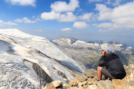 tauern: Male mountaineer looking at mountain glacier panorama view with binoculars