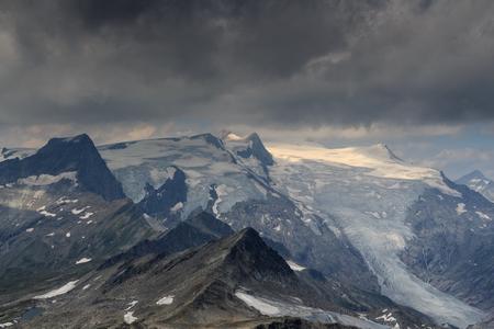 crack climbing: Dark storm clouds over mountain Grossvenediger and glacier in Hohe Tauern Alps, Austria Stock Photo