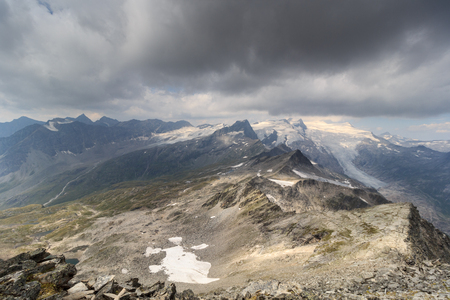 crack climb: Dark storm clouds over mountain Grossvenediger and glacier in Hohe Tauern Alps, Austria Stock Photo