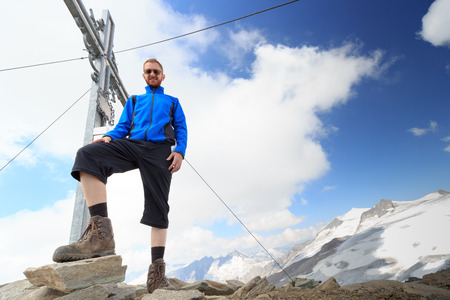 hohe tauern: Summit cross and male mountaineer on mountain Weissspitze with Grossvenediger glacier panorama in Hohe Tauern Alps, Austria