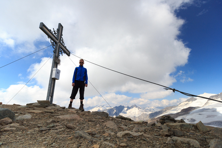 hohe tauern: Summit cross and male mountaineer on mountain Weissspitze with panorama in Hohe Tauern Alps, Austria