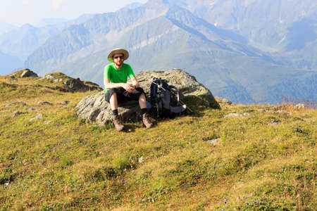 tauern: Mountaineer resting on rock in front of mountain panorama in Hohe Tauern Alps, Austria Stock Photo