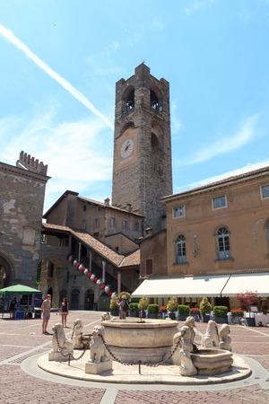 Town square Piazza Vecchia and old city tower Torre Civica in Bergamo, Citta Alta, Italy