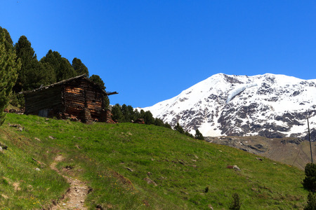 hiking path: Old wooden hut, hiking path and Mountain Palon de la Mare panorama in Ortler Alps, Italy