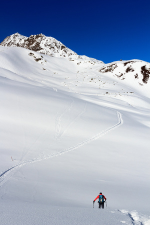 Man hiking on snowshoes and mountain snow panorama with blue sky in Stubai Alps, Austria Stock Photo