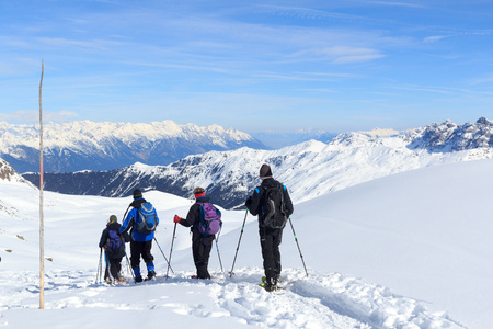 snowshoes: Group of people hiking on snowshoes and mountain snow panorama with blue sky in Stubai Alps, Austria