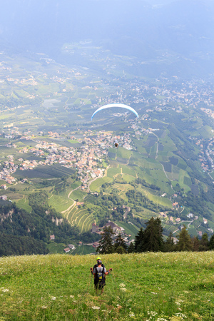 Paragliders start paragliding in front of Tirol panaroma in South Tyrol Stock Photo
