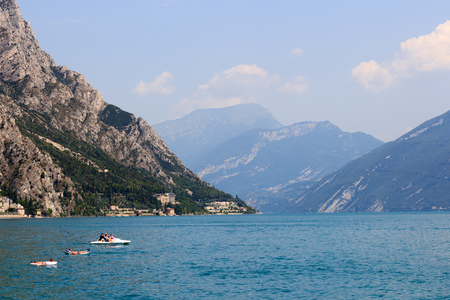 Lake Garda and mountain panorama with boat and relaxing people on airbed in Limone, Italy