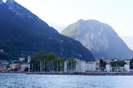 Riva del Garda town panorama with marina at Lake Garda and mountains, Italy