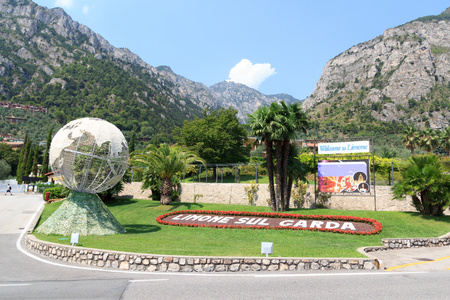 Bed of flowers with Limone sul Garda lettering, Welcome to Limone sign and mountains in Italy