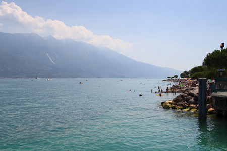 Lake Garda and mountain panorama with boats and bathing people in Limone, Italy