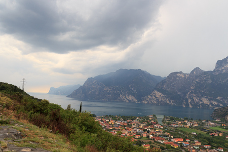 Panorama of Lake Garda, lakeside village Torbole and mountains with dark storm clouds, Italy Stock Photo