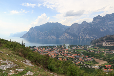 Panorama of Lake Garda, lakeside village Torbole and mountains, Italy