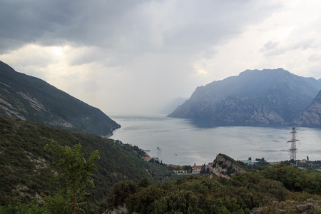 Panorama of Lake Garda and mountains with dark storm clouds, Italy Stock Photo