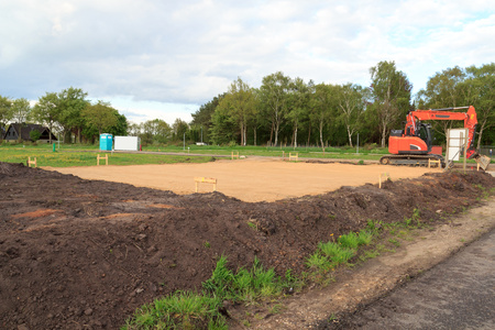 Construction site for one family house filled with sand and digger in building area after earthworks, Germany