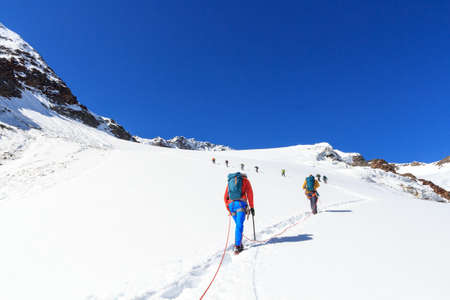 Rope team mountaineering with crampons on glacier Sexegertenferner towards Sexegertenspitze and mountain snow panorama with blue sky in Tyrol Alps, Austria