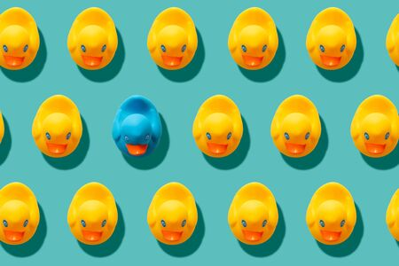 yellow rubber ducks repeating pattern on turquoise blue background with one duck different