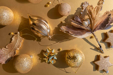 Luxurious gold Christmas flat lay pattern of various ornaments on a golden background perfect xmas card