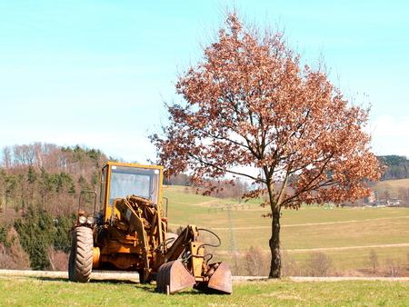 feld: Bagger auf Feld neben einen Baum