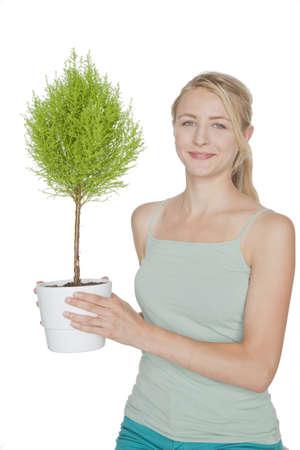 bonsai tree: young blond woman with green  bonsai tree