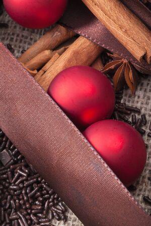 christmas scent: rojas de Navidad adornos de �rbol y ramas de canela Foto de archivo